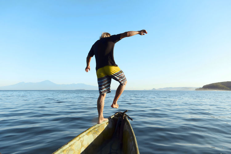 Rear view of man in sea against sky