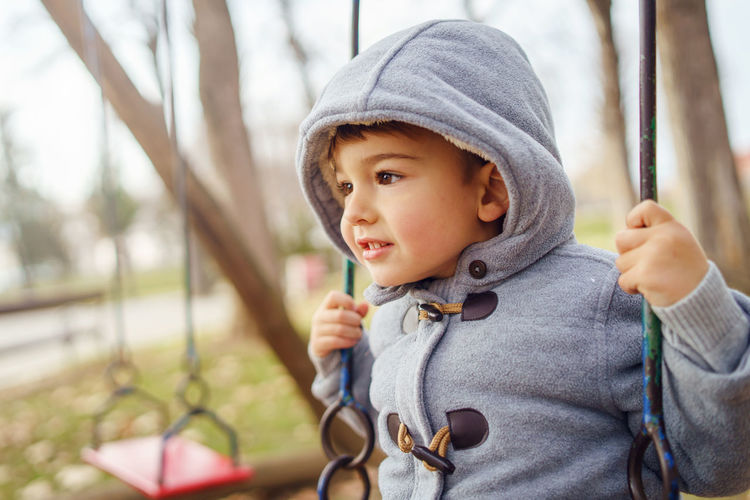 Close-up of cute boy in swing at park