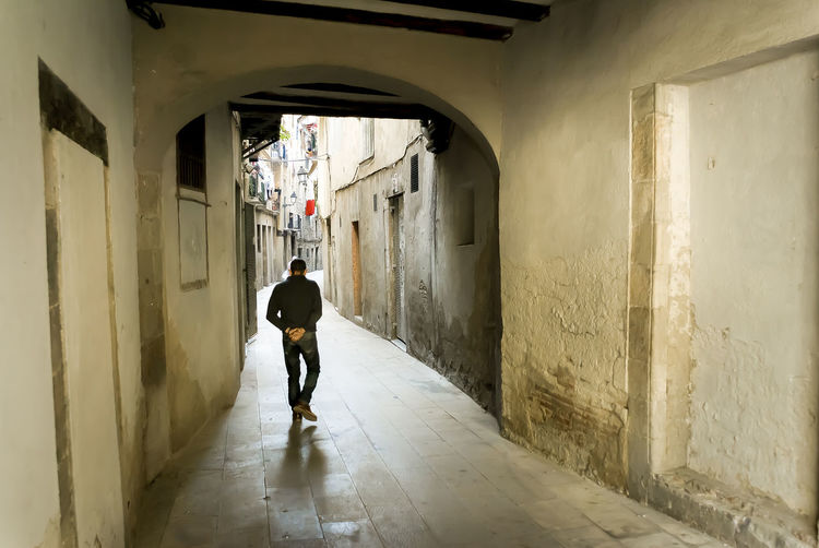 Rear view of man walking on alley amidst buildings