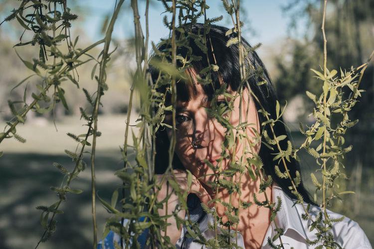 Close-up portrait of young woman against plants