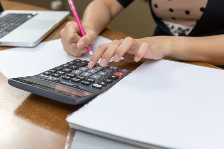 Midsection of woman using calculator on table