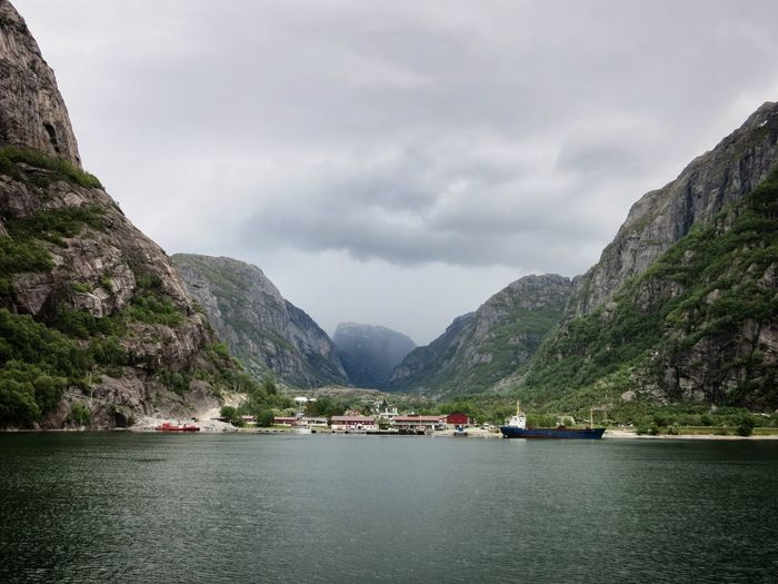 Scenic View Of Fjord Amidst Cliffs Against Cloudy Sky