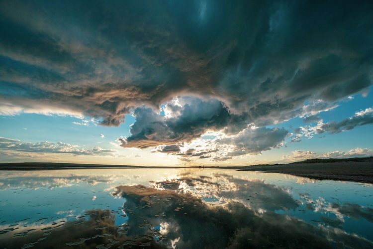 Scenic View Of Lake Against Dramatic Sky