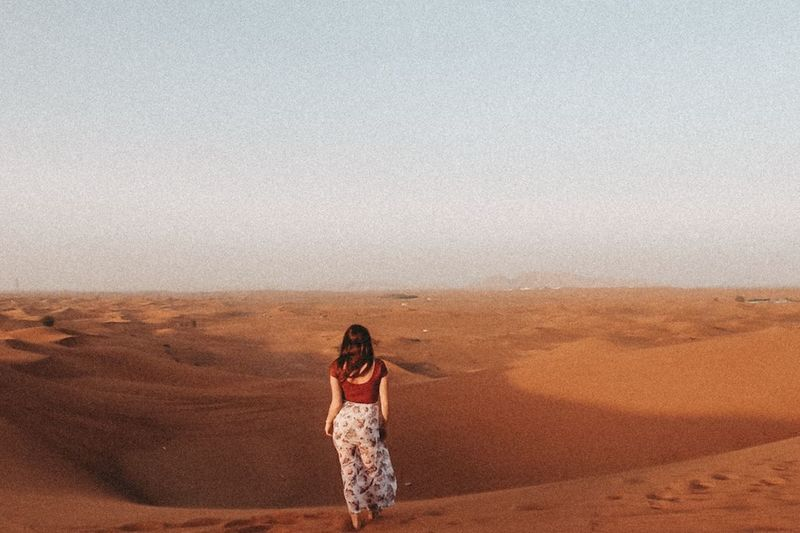 Full length of young woman standing in desert