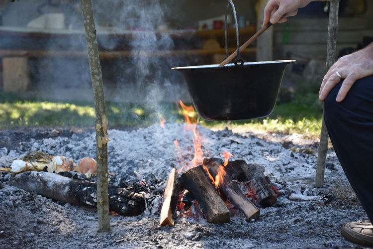 Cropped image of person preparing food at campfire