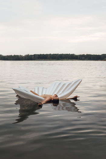 Shirtless woman floating with inflatable raft on lake against sky
