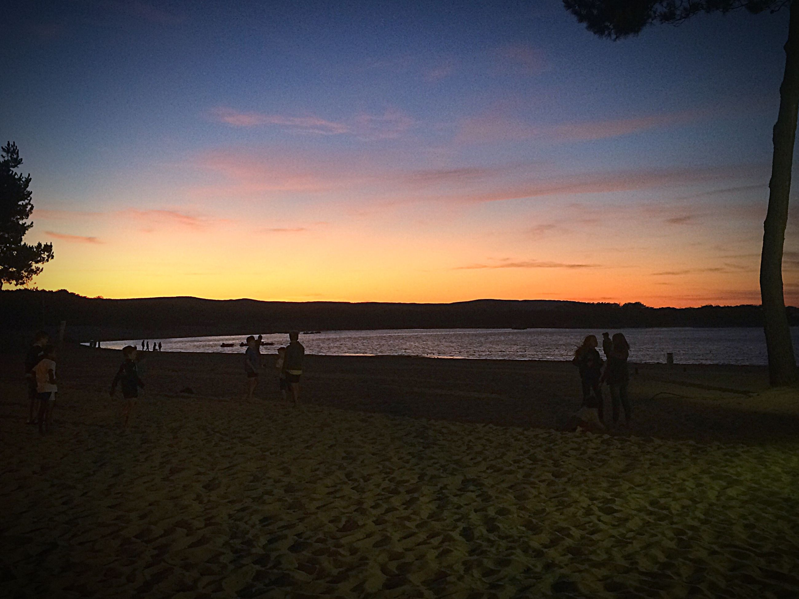 sunset, beach, scenics, tranquil scene, tranquility, sand, water, vacations, sky, incidental people, beauty in nature, idyllic, tourism, nature, tourist, travel destinations, cloud - sky, shore, sea, orange color, non-urban scene, outdoors, majestic, mountain, calm, remote, dramatic sky, atmospheric mood