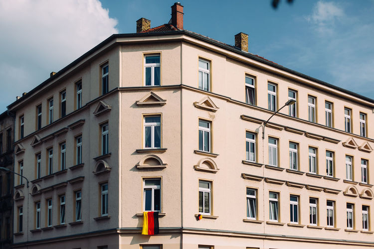 Low angle view of residential building with german flag against sky