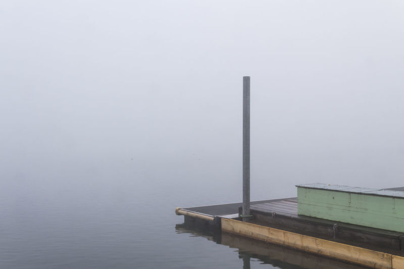 Pier over lake in foggy weather