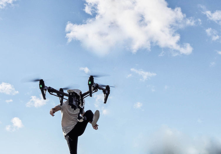 Low angle view of man with drone against sky
