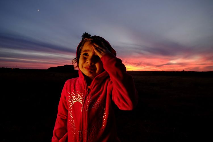 Girl crying while standing at park against sky during sunset