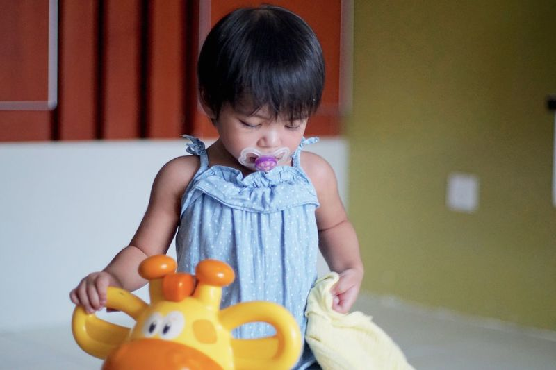 Baby Girl Playing With Toy At Home