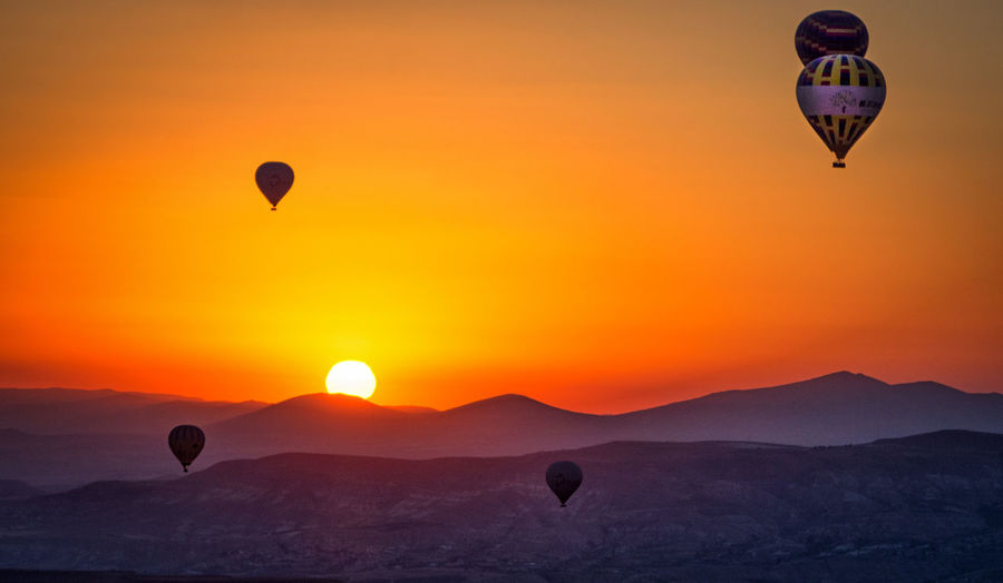 Cappadocia Adventure Air Vehicle Ballooning Festival Beauty In Nature Day Flying Hot Air Balloon Mid-air Mountain Nature No People Outdoors Parachute Paragliding Scenics Silhouette Sky Sunrise Sunrise_sunsets_aroundworld Sunset Transportation