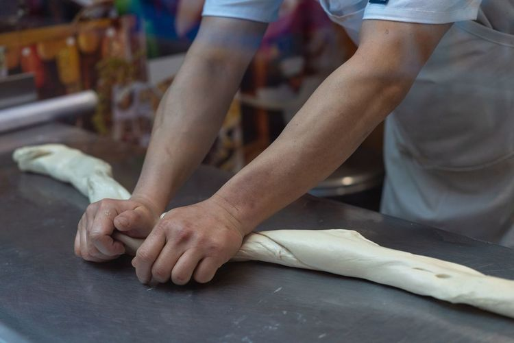 Midsection of chef kneading dough in kitchen