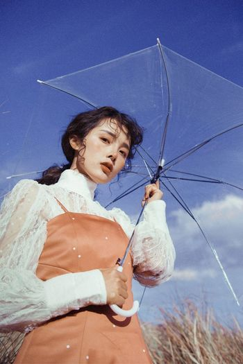 Young woman holding umbrella while standing on land against blue sky