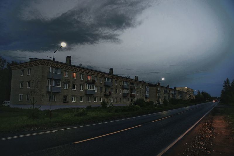 Road by buildings against sky at dusk