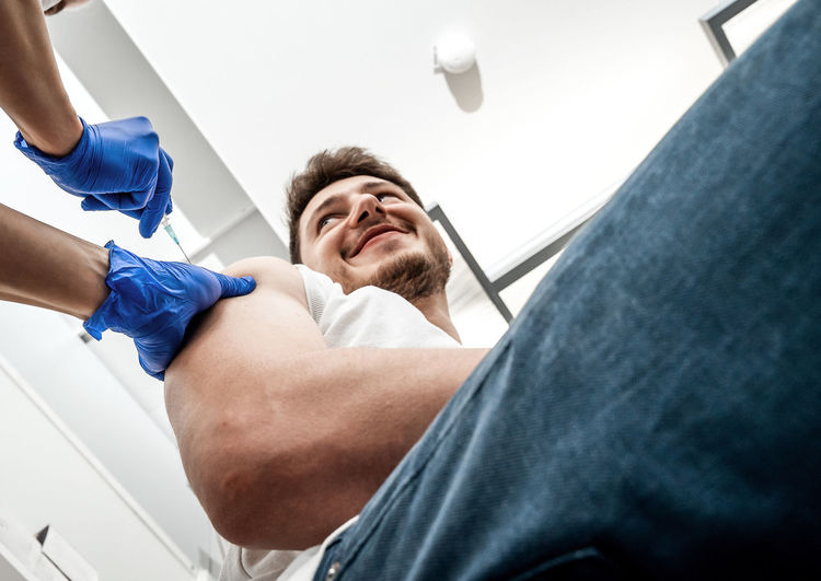 Young man receives a shot with a covid-19 vaccine dose in a vaccination center from a nurse