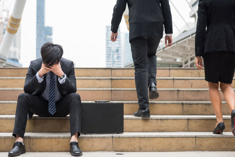 Businessman With Headache Sitting On Steps In City