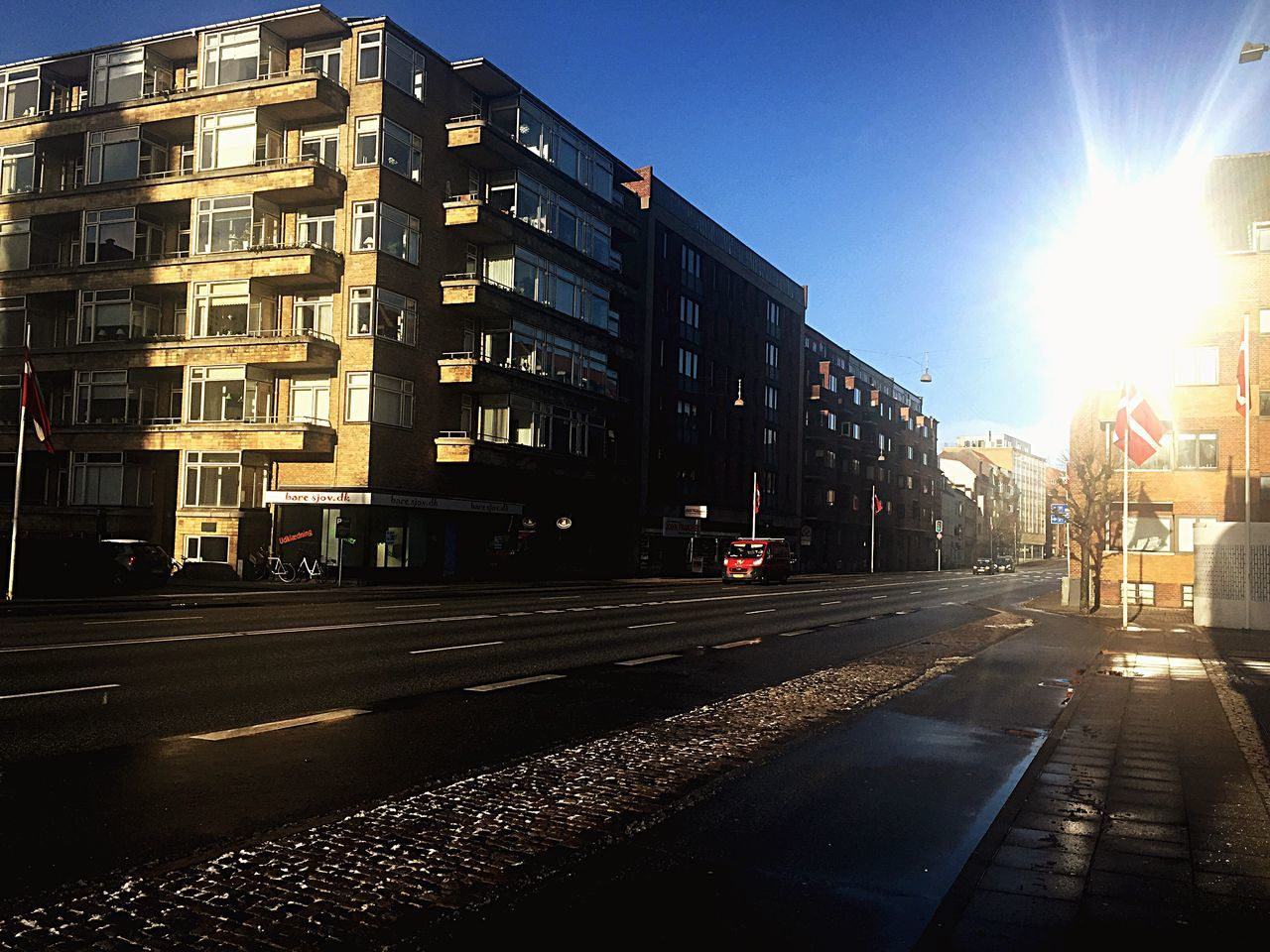 building exterior, architecture, sunlight, built structure, lens flare, city, street, outdoors, sun, road, day, sky, clear sky, no people, cityscape