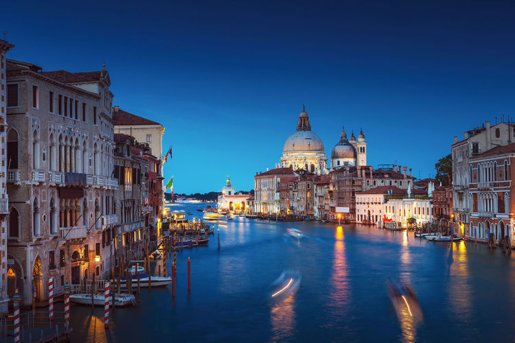 Blurred motion of boats in canal by santa maria della salute against sky at dusk