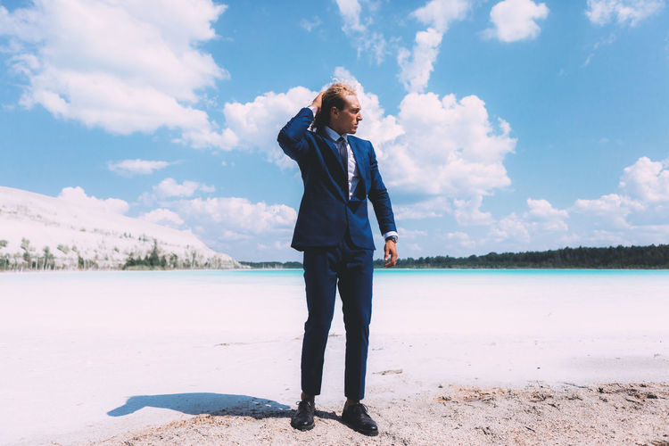Blond curly guy dressed in business suit is posing on the crystal clear lake. Trendy hairstyle, awesome shoot. Summer time. Adult Beauty In Nature Casual Clothing Cloud - Sky Day Front View Full Length Leisure Activity Lifestyles Looking Nature One Person Outdoors Real People Scenics - Nature Sky Standing Tranquil Scene Tranquility