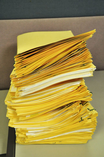 Close-up of yellow papers on table in office
