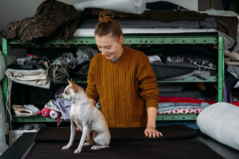 Woman and dog standing in garment factory