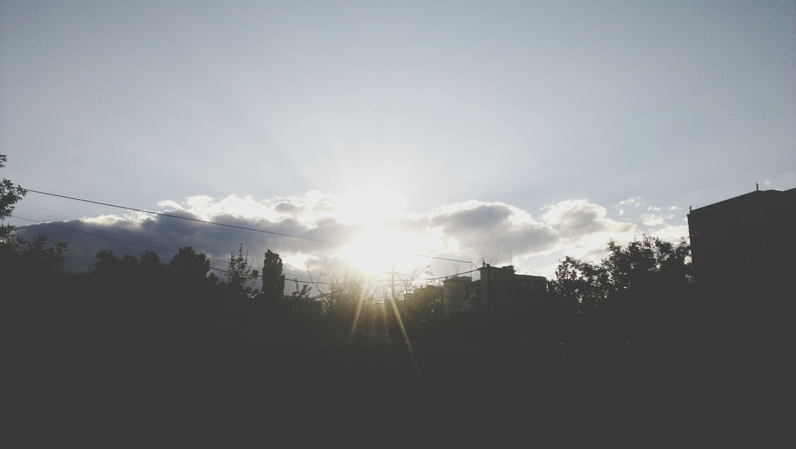 sun, silhouette, sunbeam, sunlight, tree, sky, lens flare, tranquility, sunset, nature, built structure, beauty in nature, low angle view, tranquil scene, building exterior, scenics, architecture, outdoors, no people, bright