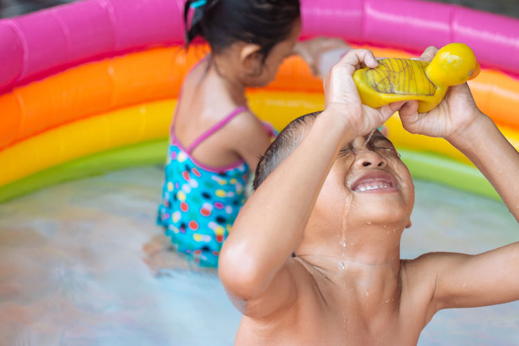 High angle view of siblings enjoying in wading pool