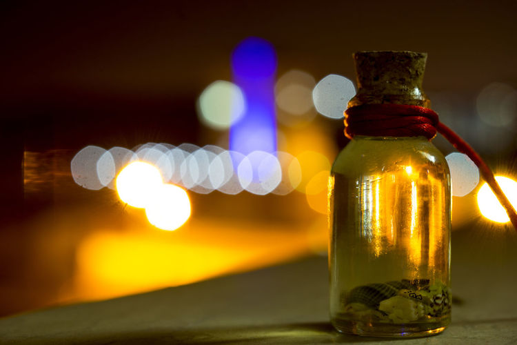 Close-up of glass bottle on table at night