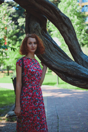 Portrait Of Young Woman Standing By Tree Trunk