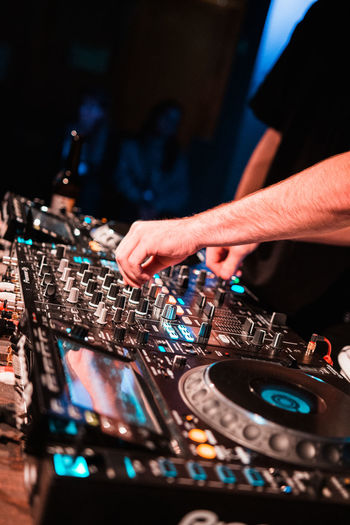 Midsection of man playing songs at nightclub