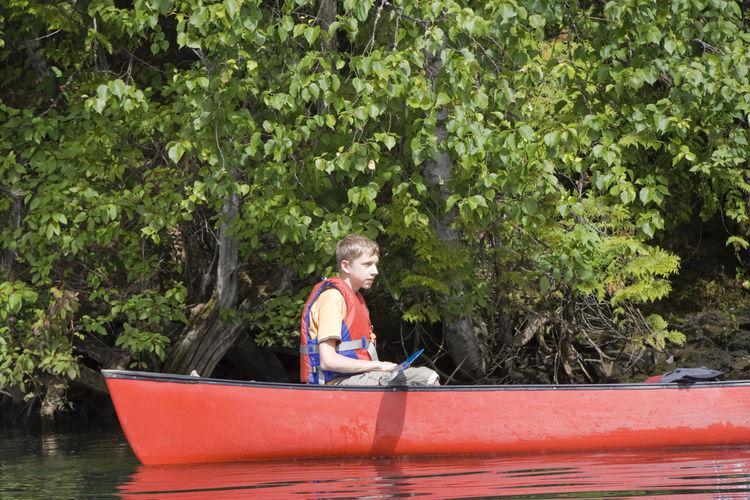 Side View Of Teenage Boy Wearing Life Jacket Canoeing On Lake
