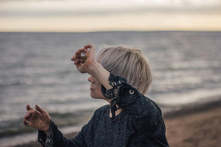 Woman holding umbrella on beach against sky