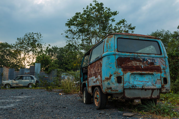 Abandoned vehicles against trees