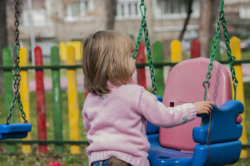 Girl holding swing at playground