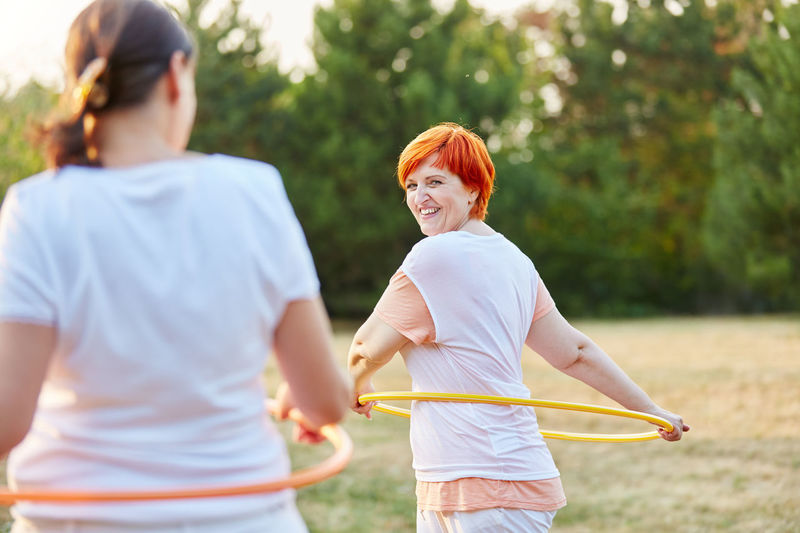 Female Friends Playing Hula Hoop On Field