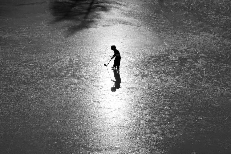Silhouette boy playing ice hokey on ice rink