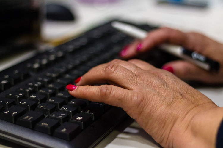 Cropped Hands Of Businesswoman Typing On Keyboard At Desk