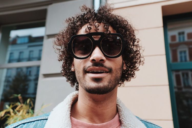 Portrait of smiling young man wearing sunglasses standing against house