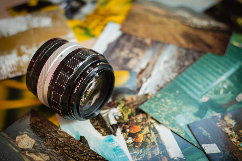 A vintage photographic lens on top of a pile of old photographs Close-up Equipment Indoors  Lieblingsteil Memories Nikkor Nikon No People Objects Photography Selective Focus Vintage Vintage Photo