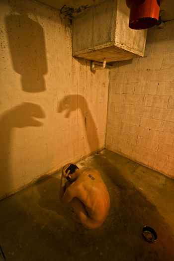 High angle view of naked man sitting in abandoned bathroom