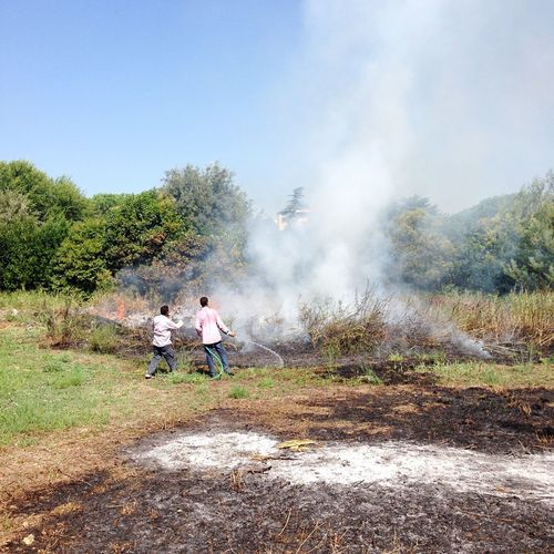 Rear view of men extinguishing fire on field