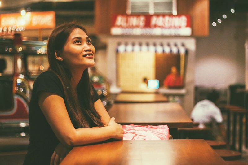 Woman Looking Away While Sitting In Illuminated Cafe At Night