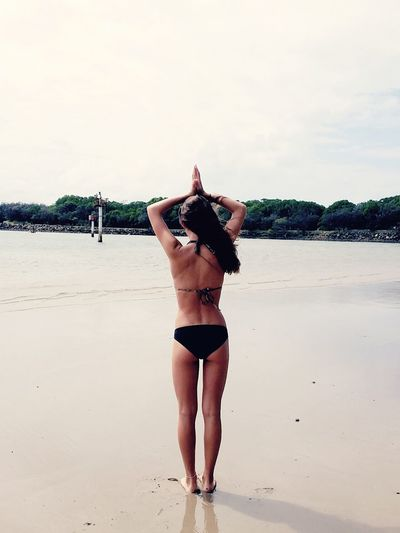 Rear View Of Woman Wearing Bikini With Hands Clasped At Beach Against Sky