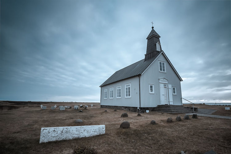 Church by cemetery against cloudy sky