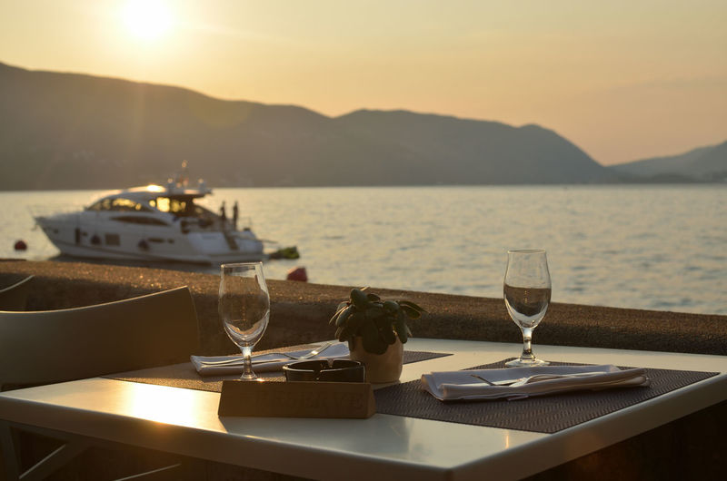 High angle view of drink on table against sea during sunset