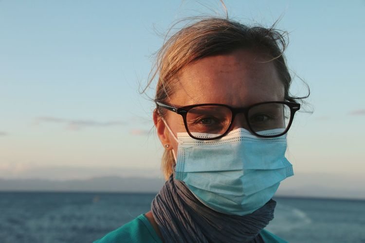 Portrait of woman wearing glasses against sky at sunset
