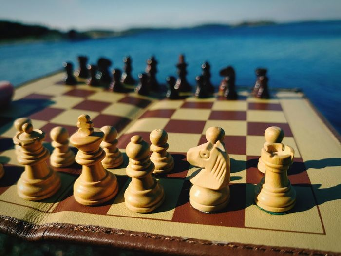 Close-up of chess board by sea