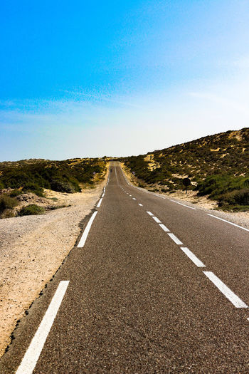 Highway Road Direction Sky The Way Forward Transportation Diminishing Perspective Road Marking Symbol Marking Sign Tranquil Scene Tranquility Nature vanishing point Landscape No People Environment Day Empty Road Blue Outdoors Dividing Line Straight Long